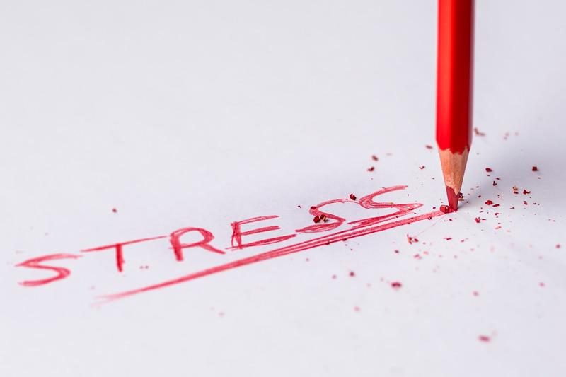 le mot stress écrit en rouge sur une feuille blanche avec appui très fort de la pointe du crayon sur la feuille