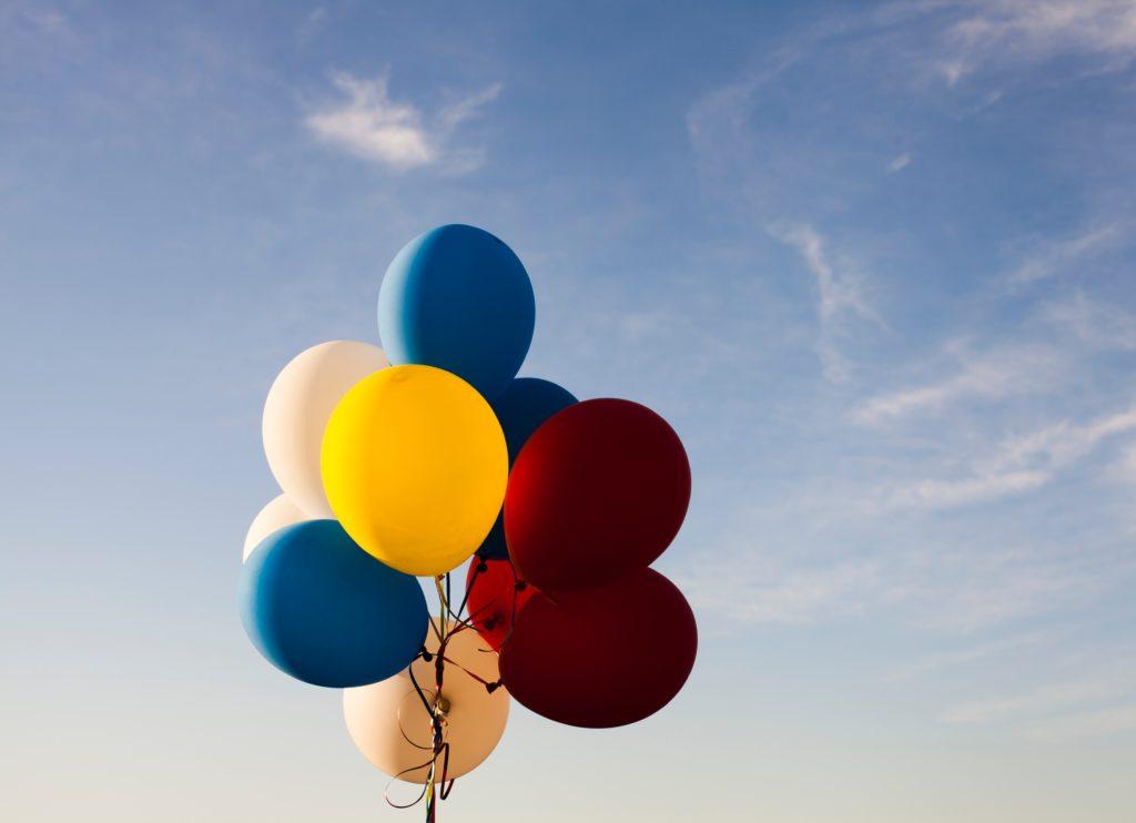 des ballons de couleur attachés comme un bouquet qui s'envolent dans le ciel
