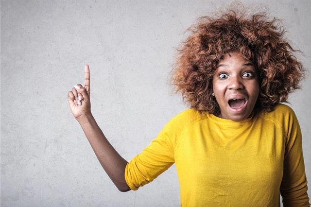 femme qui lève le doigt de la main droite  avec un visage indiquant qu'elle vient de comprendre quelque chose et la bouche grande ouverte