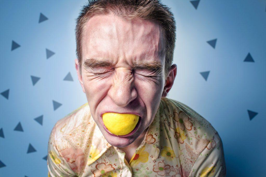 Homme avec un citron dans la bouche pour retenir sa colère
